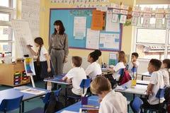 Schulmädchenschreiben auf Flip-Chart an der Front der Klasse stockfotografie