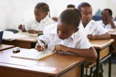 Schulmädchenschreiben an ihrem Schreibtisch in der Volksschulelektion lizenzfreie stockfotos