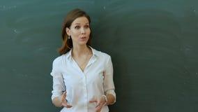 Schulmädchenschreiben mit ihrem Lehrer in einem Klassenzimmer Lizenzfreie Stockfotografie
