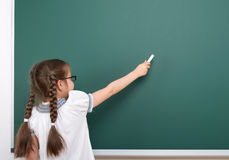 Schulmädchenschreibenskreide auf einer Tafel, leerer Raum, Bildungskonzept Stockfotografie