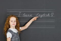 Schulmädchenzeichnung und Zeigen auf Tafel Lizenzfreie Stockfotos