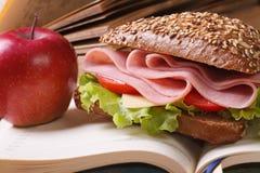 Schulmahlzeit: ein Schinkensandwich und ein Apfel auf offenem Notizbuch Lizenzfreie Stockfotos