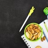 Schulmahlzeit in einem grünen runden Behälter mit Plätzchen und Mandeln auf einem dunklen Hintergrund mit Griffen und Notizbücher Stockfotografie