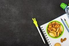 Schulmahlzeit in einem grünen runden Behälter mit Plätzchen und Mandeln auf einem dunklen Hintergrund mit Griffen und Notizbücher Lizenzfreie Stockfotos
