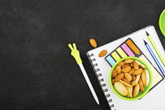Schulmahlzeit in einem grünen runden Behälter mit Plätzchen und Mandeln auf einem dunklen Hintergrund mit Griffen und Notizbücher Lizenzfreie Stockfotografie