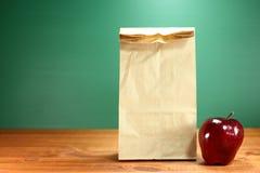 Schulmahlzeit-Sack, der auf Lehrer Desk sitzt Stockbild