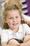 Schulmädchen, das in der Hauptkategorie sitzt Lizenzfreie Stockbilder