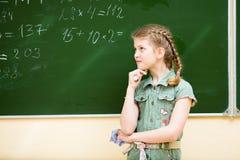 Schulmädchen, das an der Tafel denkt Stockbild