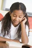 Schulmädchen, das ein Buch in der Kategorie liest Lizenzfreie Stockfotografie