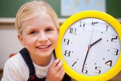 Schulmädchen, das eine Borduhr zeigt Stockbild