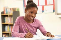 Schulmädchen, das im Klassenzimmer studiert Stockfoto