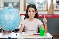 Schulmädchen, das oben Daumen am Schreibtisch gestikuliert Lizenzfreie Stockbilder
