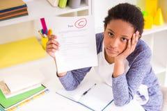 Schulmädchen, das Testergebnisse zeigt Stockfotografie