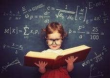 Schulmädchen des kleinen Mädchens des Wunderkind mit einem Buch vom blackboar Stockbild