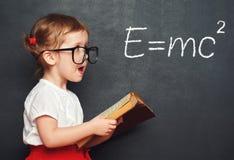Schulmädchen des kleinen Mädchens des Wunderkind mit einem Buch vom blackboar Stockbilder