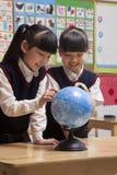 Schulmädchen, die eine Kugel im Klassenzimmer betrachten Stockbild