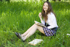 Schulmädchen im Park las Buch Stockbilder