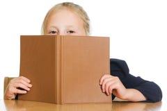 Schulmädchen versteckt sich hinter einem Buch Stockfoto