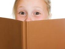 Schulmädchen versteckt sich hinter einem Buch Lizenzfreies Stockfoto