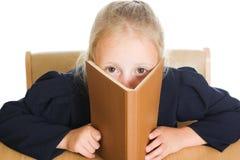 Schulmädchen versteckt sich hinter einem Buch Stockbild