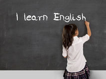 Schulmädchenschreiben lerne ich Englisch mit Kreide auf Tafelschule Lizenzfreies Stockfoto