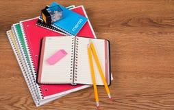 Schulnotizbücher und -Zubehör auf einem hölzernen Desktop Stockbilder