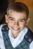 Schulpflichtiger Junge, der an der Kamera lächelt Lizenzfreie Stockfotos
