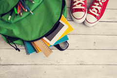 Schulrucksack auf hölzernem Hintergrund Lizenzfreies Stockfoto