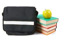 Schulrucksack, Bücher und ein Apfel Stockbilder