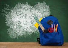 Schultasche auf Schreibtischvordergrund mit Tafelgraphiken von Bildungsikonenzeichnungen lizenzfreie stockbilder