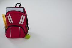 Schultasche mit verschiedenen Versorgungen und Apfel Lizenzfreie Stockfotografie