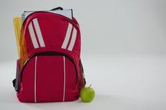 Schultasche mit verschiedenen Versorgungen und Apfel auf weißem Hintergrund Stockfotografie