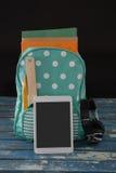 Schultasche mit verschiedenen Versorgungen und digitale Tablette auf Tabelle Lizenzfreies Stockbild