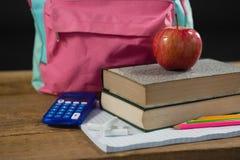 Schultasche, Versorgungen und Apfel auf Holztisch Stockbild