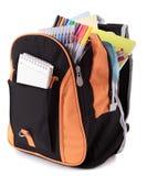 Schultasche voll mit Bleistiftkasten, Versorgungen, lokalisiert auf weißem Hintergrund Stockfotografie
