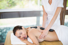 Schulterfreie Frau, die Steinmassage am Gesundheitsbadekurort genießt Stockfotografie