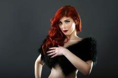 Schulterfreie Rothaarigefrau, die ihre Brüste mit einem schwarzen Pelzmantel bedeckt Lizenzfreie Stockfotografie