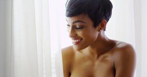 Schulterfreie schwarze Frau, die heraus Fenster und das Lächeln schaut Stockbild