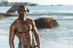 Schulterfreier afrikanischer schwarzer Mann auf Strand Lizenzfreie Stockfotografie
