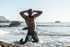 Schulterfreier afrikanischer schwarzer Mann auf Strand Stockbild