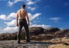 Schulterfreier starker Mann steht auf dem Berg Stockfoto
