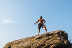 Schulterfreies Porträt des amerikanischen Mannbodybuilders des starken Schwarzafrikaners, der auf dem Felsen aufwirft Blauer Hint Stockbild