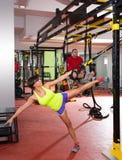 Schulungsübungen der Eignung TRX an der Turnhallenfrau und -mann Stockfoto