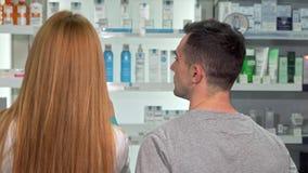 Schuss der hinteren Ansicht eines Apothekers und des Kunden, die am Drugstore sprechen stock video footage