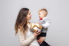 Schuss einer entzückenden Öffnung des kleinen Jungen stellt sich mit seiner Mutter auf seinem ersten Geburtstag dar Lizenzfreie Stockfotografie