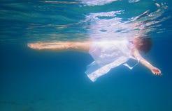 Schuss einer Frau im Meer mit weißem Kleid lizenzfreies stockbild