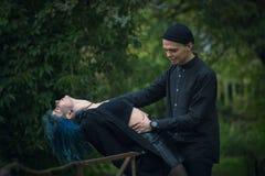 Schuss eines gefährlichen Mannes, der eine erschrockene blaue Haarfrau ergreift Stockfoto