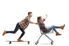 Schuss in voller Länge eines jungen Kerls, der ein longboard reitet und ein Mädchen in einem Einkaufswagen lokalisiert auf weißen lizenzfreie stockfotografie