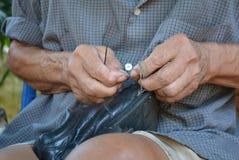 Schuster, der mit einem Messer arbeitet Stockbild