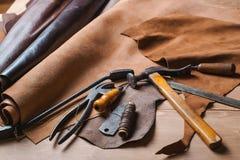 Schusterwerkzeuge im Seminar über den Holztisch Beschneidungspfad eingeschlossen Stockfoto